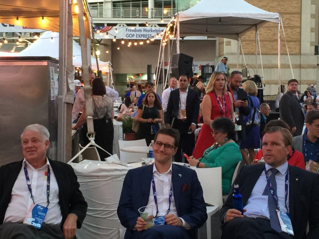 חברי מפלגה רפובליקנים צופים בבית הקפה מחוץ לארנה בשידור חי על מסך ענק של נאומי הפוליטיקאים